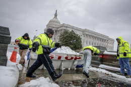 Workmen clear snow from a security barricade on Capitol Hill in Washington, Tuesday, March, 14, 2017. A late-season storm is dumping a messy mix of snow, sleet and rain on the mid-Atlantic, complicating travel, knocking out power and closing schools and government offices around the region.  (AP Photo/J. Scott Applewhite)