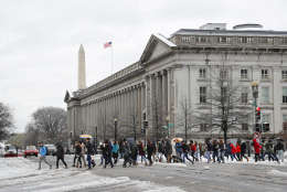 People cross 15th Street NW at the Treasury building, looking toward the Washington Monument in downtown Washington, Tuesday, March 14, 2017. A late-season storm is dumping a messy mix of snow, sleet and rain on the mid-Atlantic, complicating travel, knocking out power and closing schools and government offices around the region. (AP Photo/Pablo Martinez Monsivais)