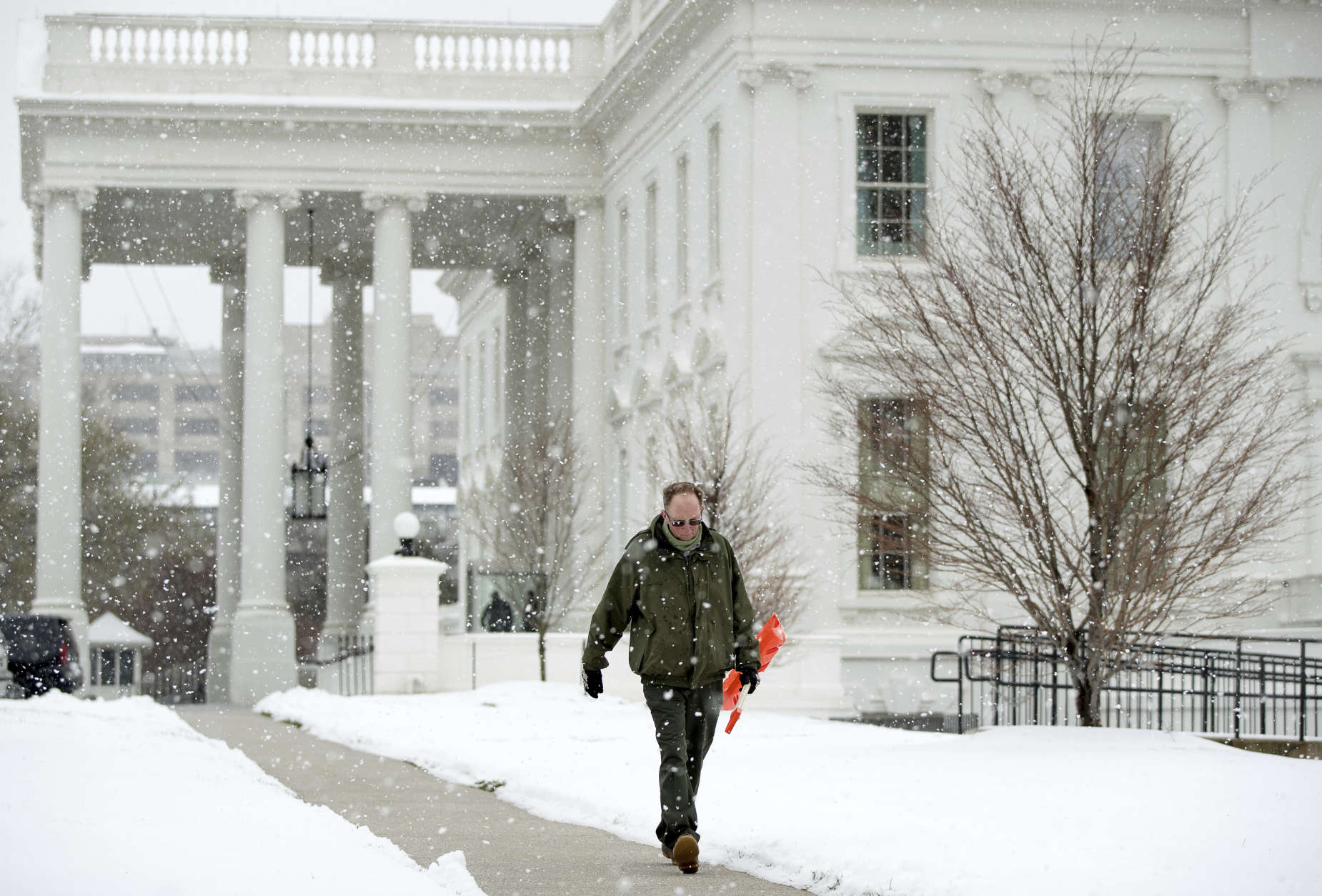 A worker walks through the falling snow outside the White House in Washington, Tuesday, March 14, 2017. A sloppy, blustery late-season storm lashed the Northeast with sleet and more than a foot of snow in places, paralyzing much of the Washington-to-Boston corridor after a remarkably mild February had lulled people into thinking the worst of winter was over.  (AP Photo/Andrew Harnik)