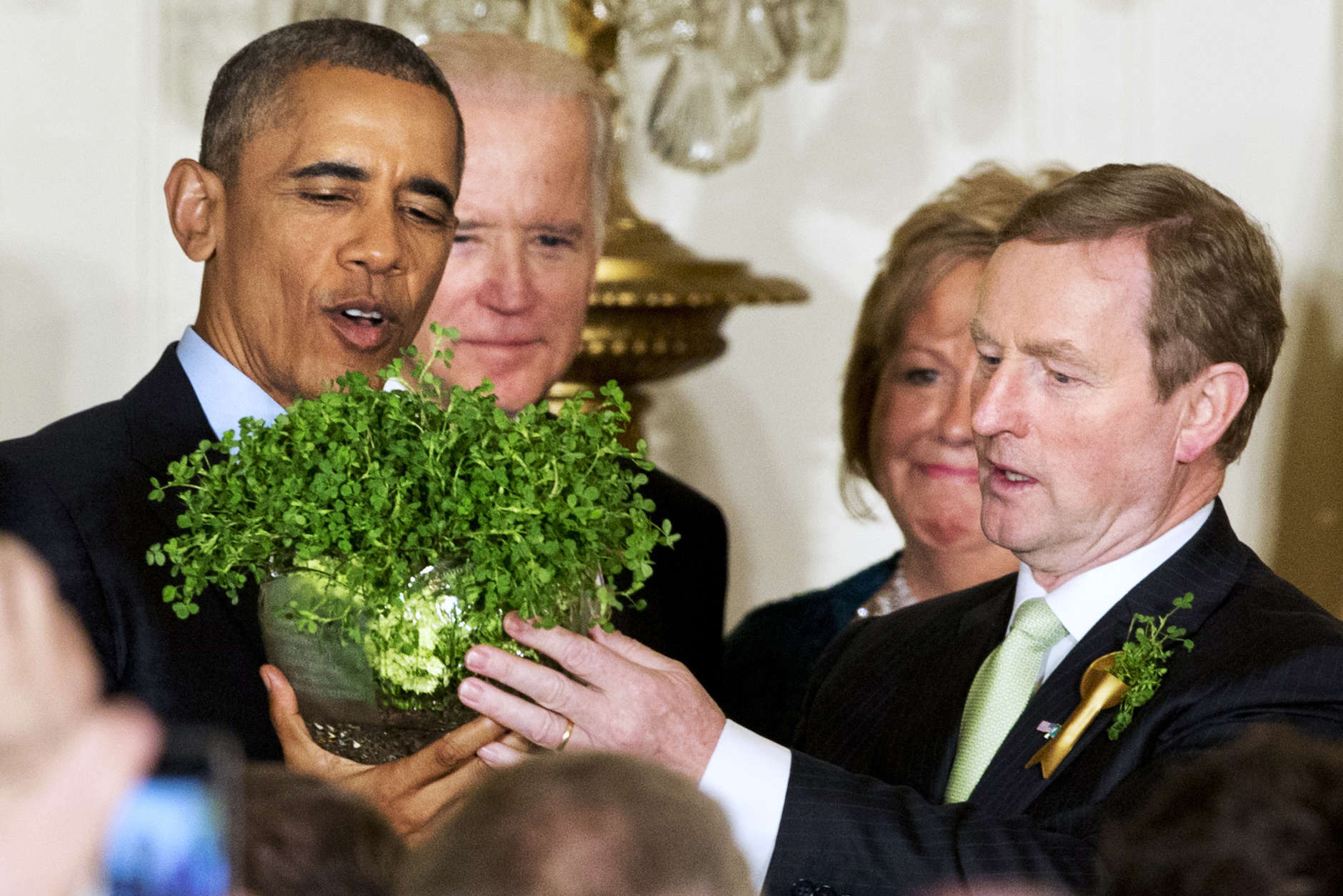 President Barack Obama, left, with Vice President Joe Biden, and Ireland Prime Minister Enda Kenny, right, with his wife Fionnuala Kenny, hold up a bowl of shamrocks during a reception in honor of St. Patrick's Day in the East Room of the White House in Washington, Tuesday, March 15, 2016. Obama is celebrating his eighth St. Patrick's Day in the White House. (AP Photo/Jacquelyn Martin)