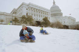 Allen and Lauren Haywood, top, both of Washington, slide down the snow-covered grounds of he Capitol, March 14, 1993. At right is Aubrey Parsons of Washington. A severe winter storm dumped nearly a foot of snow in the nation's capital over the weekend. (AP Photo/Mark Wilson)
