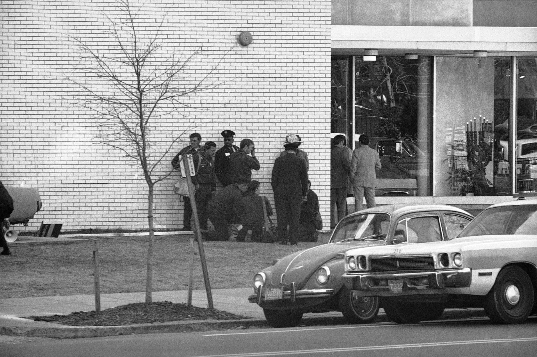 Police and rescue workers give first aid to a victim outside B'Nai B'Rith in Washington on Wednesday, March 9, 1977. Gunmen have taken hostages inside. (AP Photo)