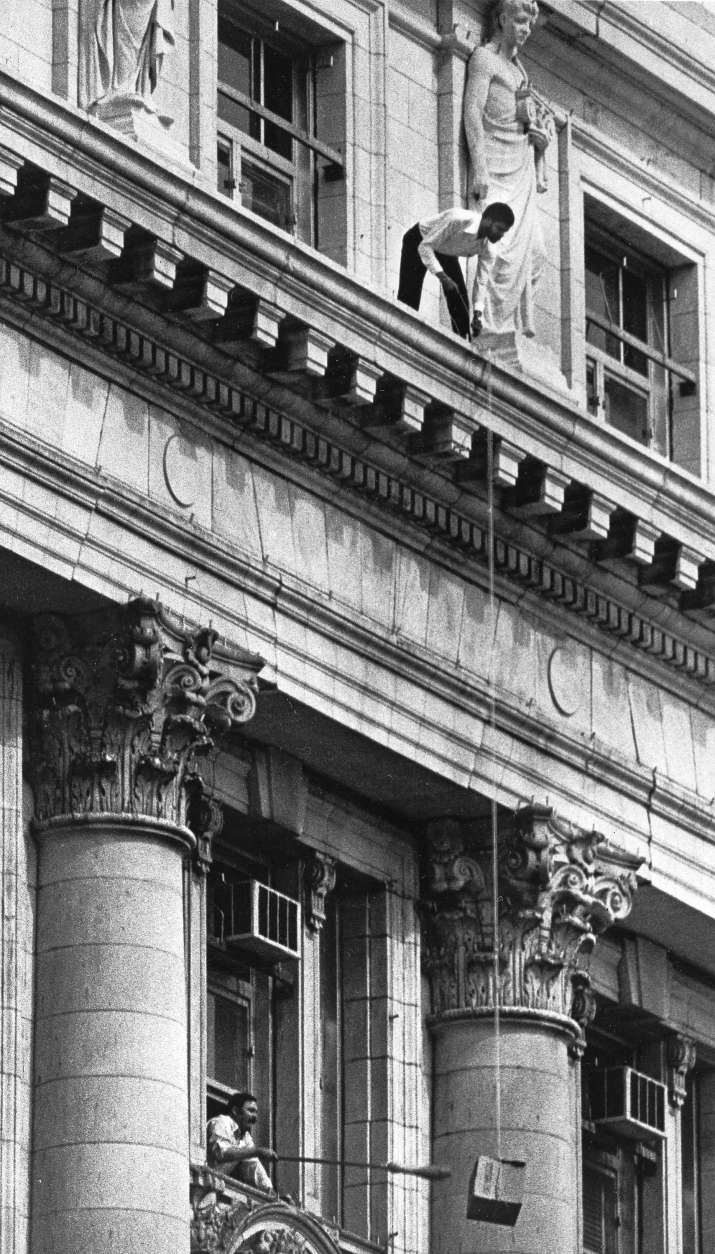 A man identified by police as one of the hostages hauls up by rope a box of food to the top floor of the District Building in Washington, where gunmen are holding hostages, March 10, 1977. A man on the floor beneath uses a broom to push the box away from the building. (AP Photo)
