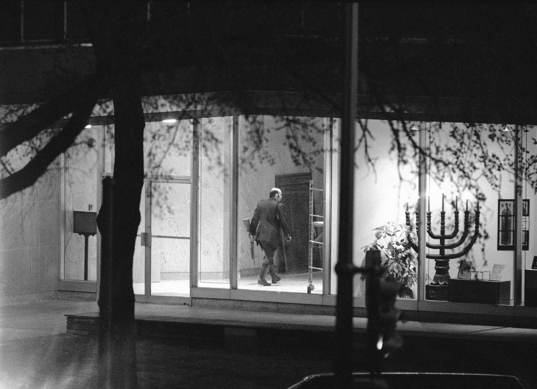 A policeman carries a shotgun as he walks inside B'Nai B'Rith headquarters in Washington on Thursday, March 10, 1977 where gunmen are holding people hostage. At right is a Menorah, holy candelabra. (AP Photo/Charles Tasnadi)