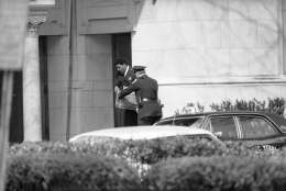 Police officers deliver a box of food to a door at the Islamic Center in Washington on March 10, 1977 where gunmen are holding 14 hostages on Thursday. The center is one of three buildings where terrorists are holding captives. (AP Photo)