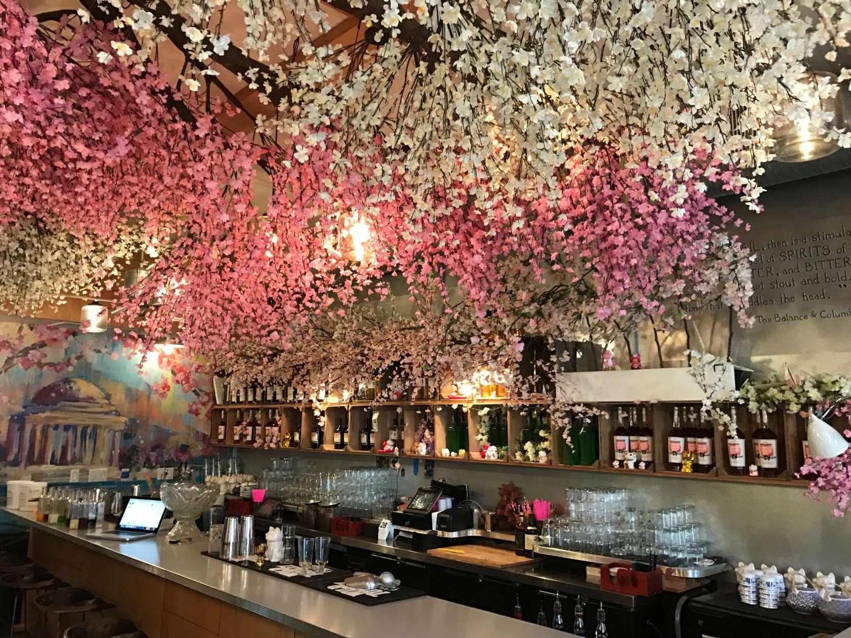 The Cherry Blossom Pop-Up Bar (or Cherry Blossom PUB) encompasses two themes. At Southern Efficiency, pink and white blossom branches creep up the side wall and hang from the ceiling. A mural of the Jefferson Memorial draped in cherry blossoms covers the back wall. (WTOP/Rachel Nania)