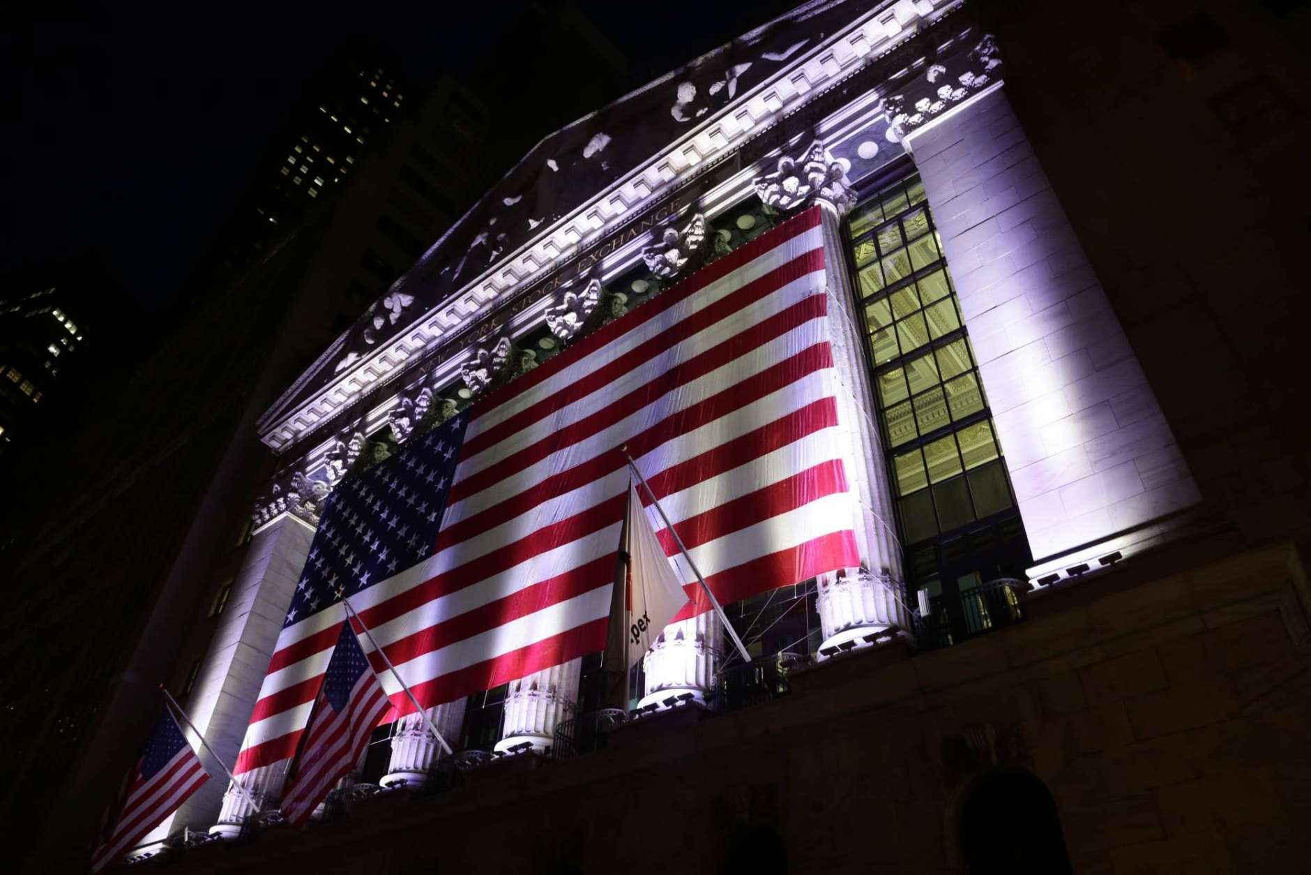 FILE - In this Friday, Feb. 17, 2017, file photo, an American flag hangs on the front of the New York Stock Exchange. Stocks around the world sank Monday, March 27, 2017, on worries that the Trump White House may not be able to help businesses as much as once thought. Many of the trends that have been in place since Election Day went into sharp reverse: The dollar's value sank against other currencies, as did bank stocks, while prices jumped for Treasury bonds. (AP Photo/Peter Morgan, File)