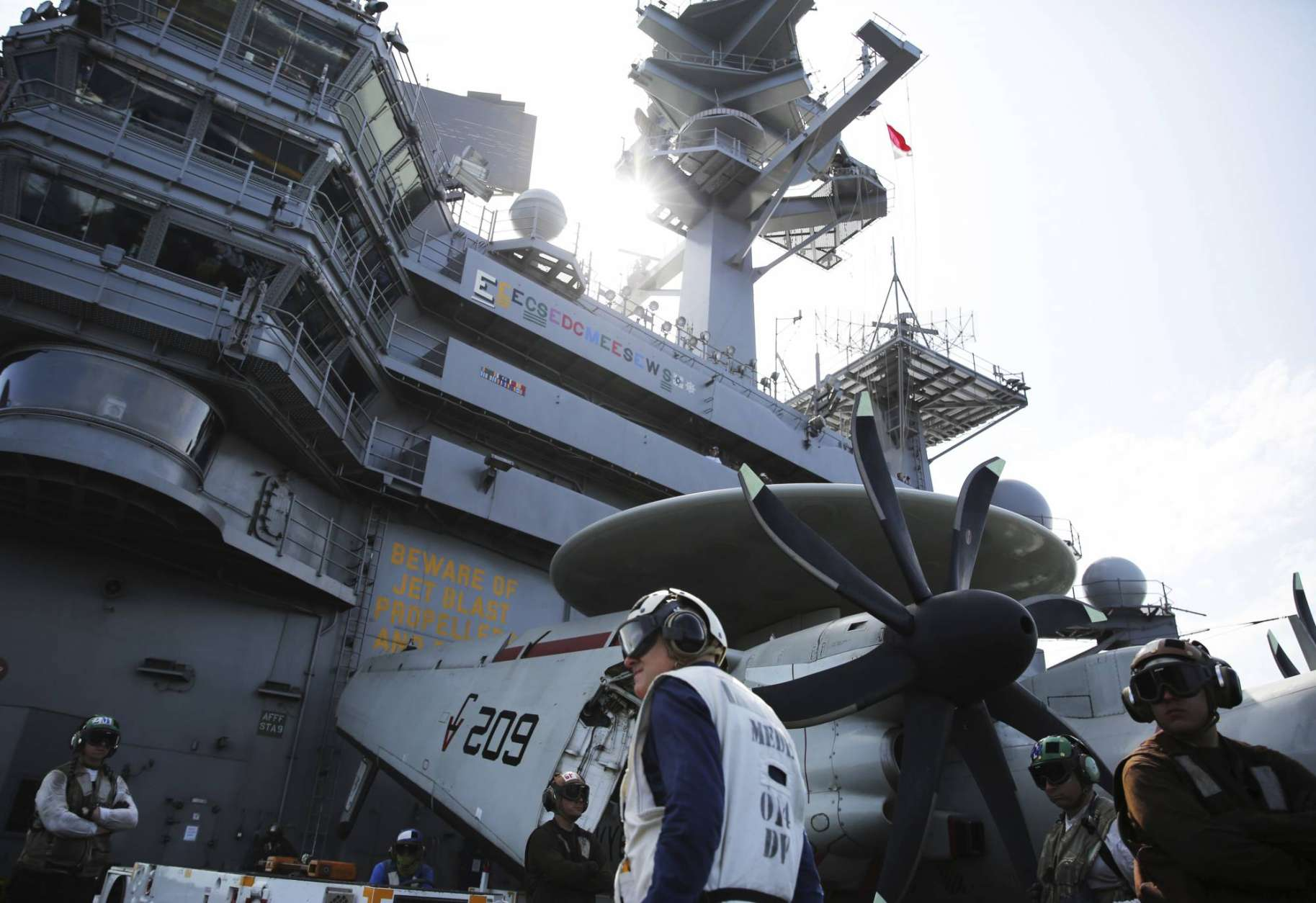 In this Monday, March 20, 2017 photograph, crew man the flight deck of the USS George H.W. Bush as it travels toward the Strait of Hormuz. The arrival of the nuclear-powered aircraft carrier to the Persian Gulf marks the first such deployment under new U.S. President Donald Trump. (AP Photo/Jon Gambrell)