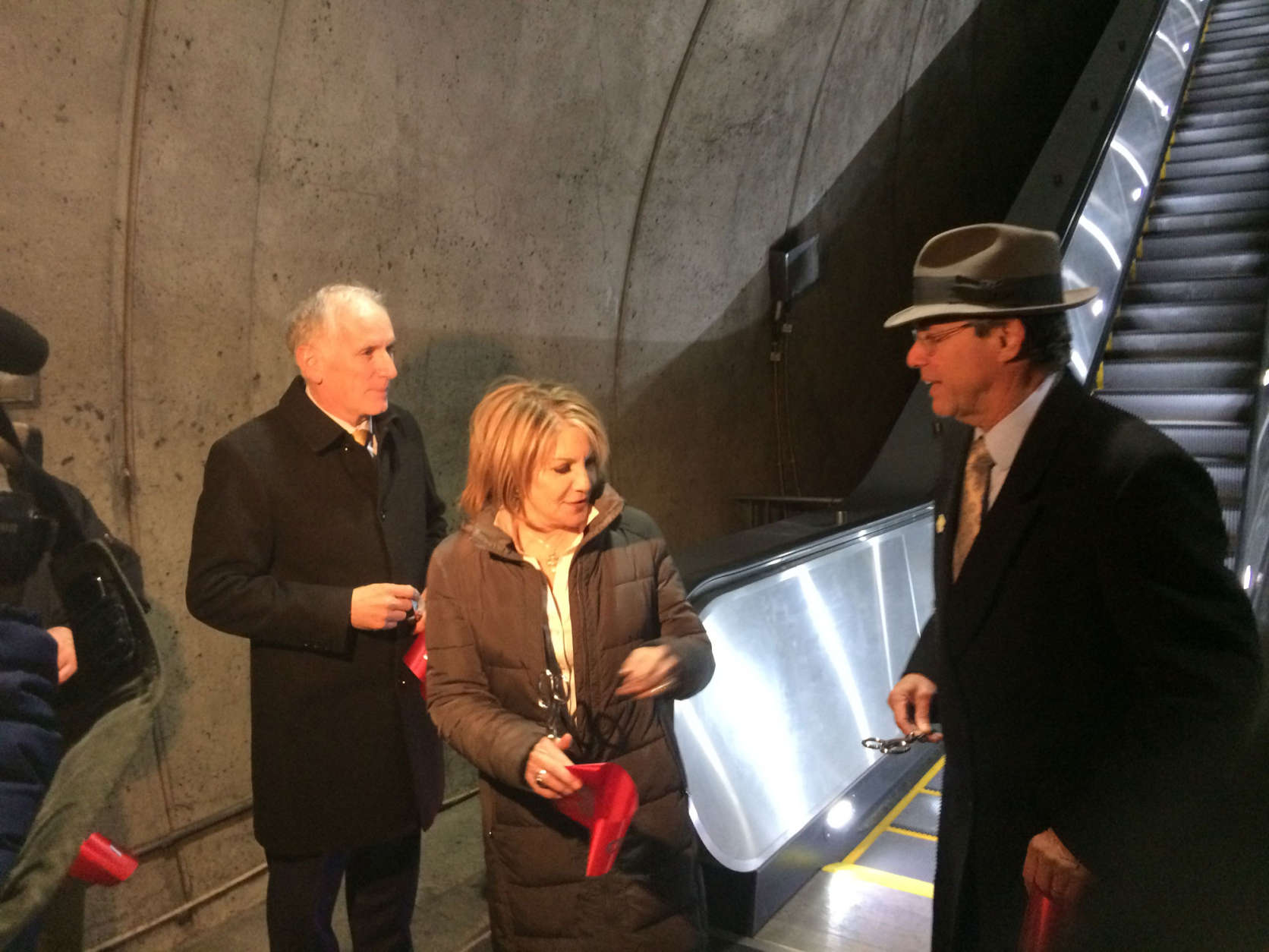 Metro General Manager Paul Wiedefeld; Jane Fairweather, of the Bethesda Chamber of Commerce task for on Metro, and Montgomery County Council President Roger Berliner cut the ribbon on the new escalators at the Bethesda Metro station. (WTOP/Dick Uliano)