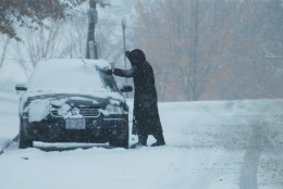 A woman sweeps wet snow off a car in Northwest Washington during a heavy snowfall in early March -- yes, March -- 2015. (WTOP/Dave Dildine)