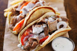 greek gyros with tzatziki sauce and fries on parchment paper. Shot with selective focus in natural light.