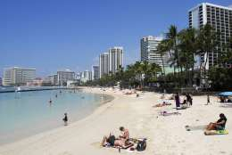 In this Monday, March 13, 2017 photo, people relax on the beach in Waikiki in Honolulu. Hawaii has filed a lawsuit challenging President Donald Trump's revised travel ban, saying the executive order could harm the state's strong tourist economy. (AP Photo/Caleb Jones)