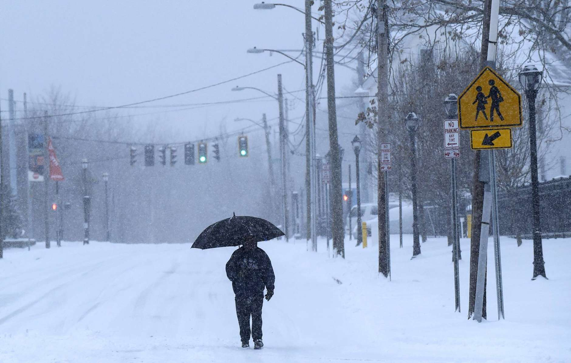 Gerald Maurice trudges along Hawthorn Street as snow falls in Hartford, Conn., on Tuesday, March 14, 2017. (Patrick RaycraftHartford Courant via AP)