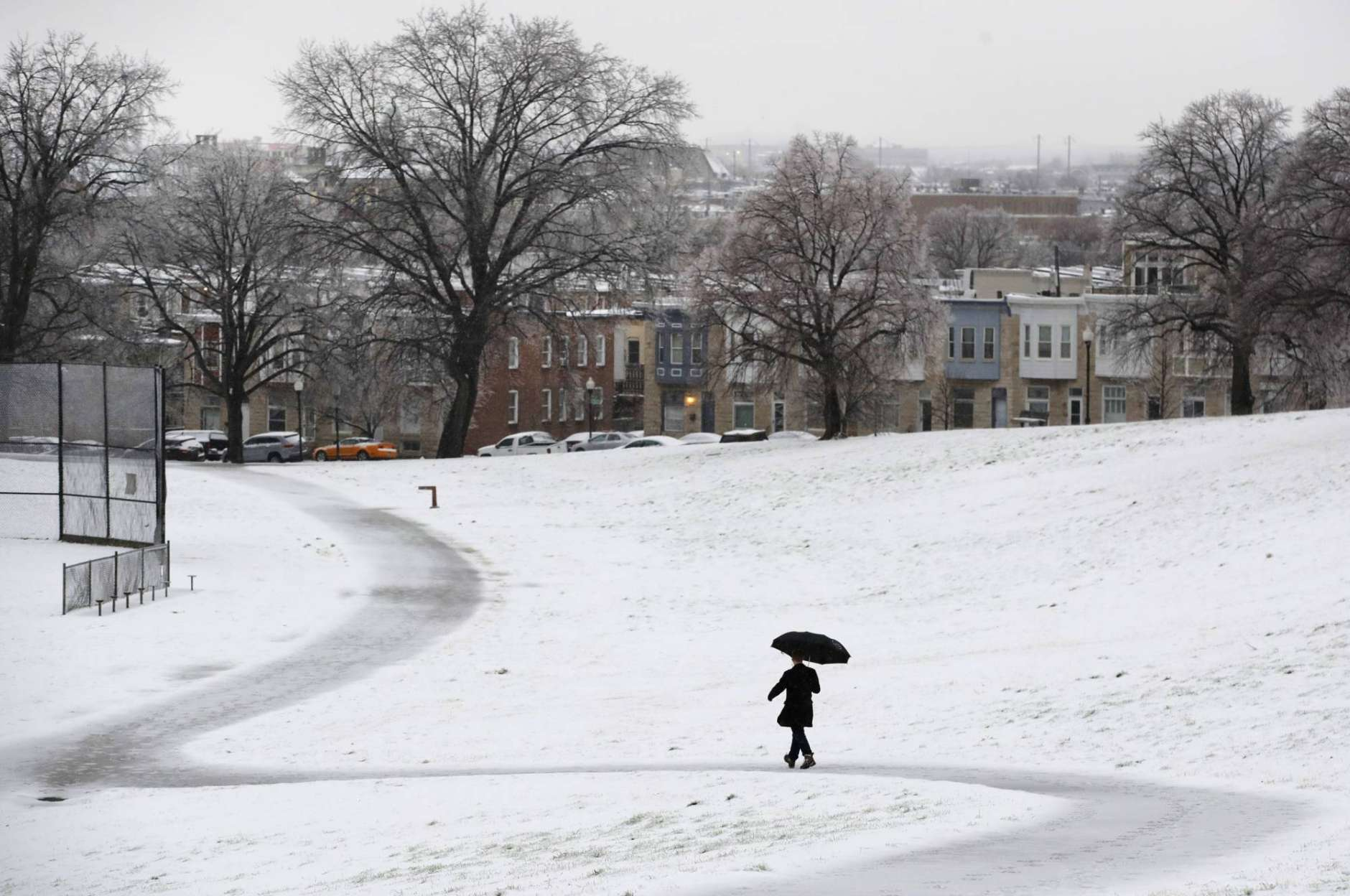 A man walks through a park in Baltimore, Tuesday, March 14, 2017, as a winter storm moves through the region. (AP Photo/Patrick Semansky)