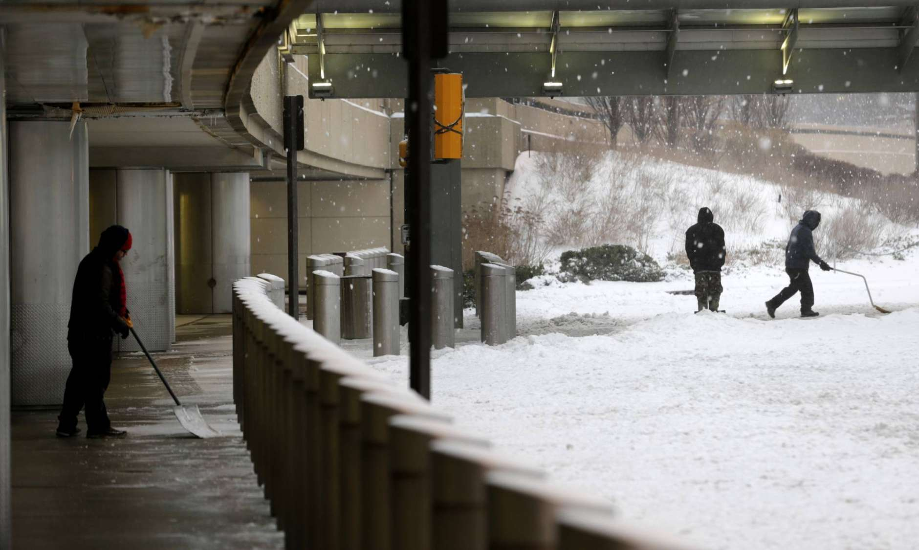 People shovel snow at Newark Liberty International Airport in Newark, N.J., Tuesday, March 14, 2017. A storm pounded the Northeast with more than a foot of snow in places Tuesday, paralyzing much of the Washington-to-Boston corridor after a remarkably mild February had lulled people into thinking the worst of winter was over. (AP Photo/Seth Wenig)