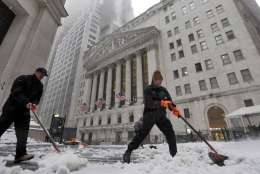 Snow is shoveled from a sidewalk adjacent to the New York Stock Exchange, Tuesday, March 14, 2017. New York Gov. Andrew Cuomo has declared a state of emergency Tuesday for all of New York's 62 counties, including New York City's five boroughs. (AP Photo/Richard Drew)