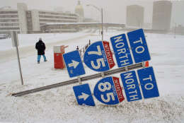 A pedestrian walks through the snow March 13, 1993, in Atlanta. Interstate signs were knocked down by the windy conditions. That snowstorm, which dumped 13.9 inches of snow at Dulles International Airport, enveloped the eastern third of the country. (AP Photo/Curtis Compton)