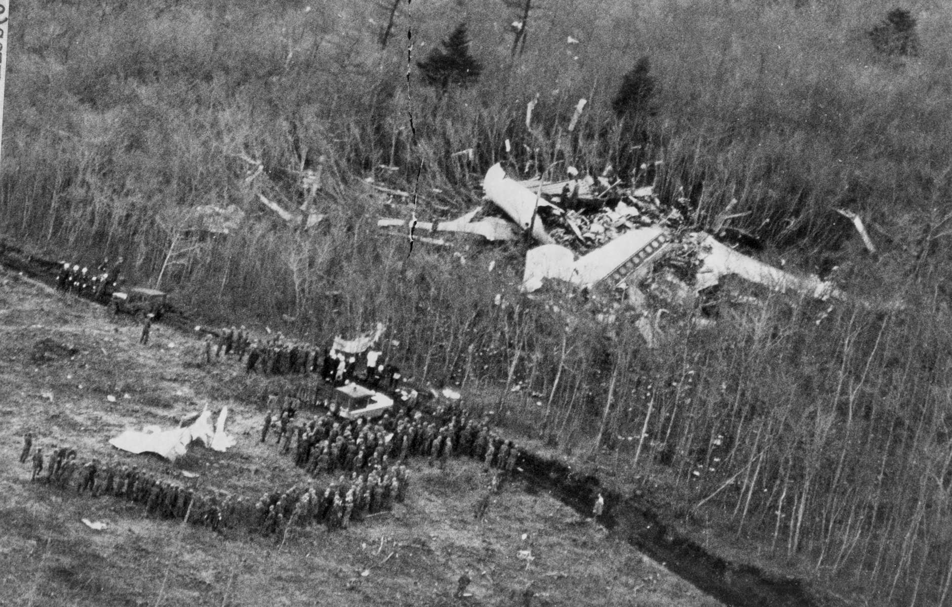 Rescue workers gather around bits of wreckage, lower left, at scene of the crash of a BOAC 707 jet on Mt. Fuji in Japan,  March 5, 1966. All 124 persons aboard were killed in the crash. In background is part of Jetliner. (AP Photo)