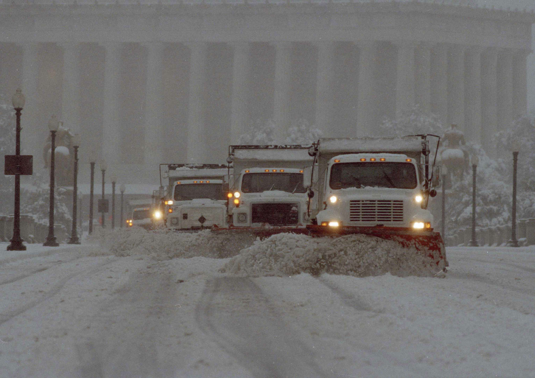 A line of trucks with snow plows push snow across the Memorial Bridge heading from Washington into Arlington, Va. as snow fell in the Washington area, March 13, 1993. The major storm battered the area snarling roads and closing museums. The Lincoln Memorial is in the background. (AP Photo/Mark Wilson)