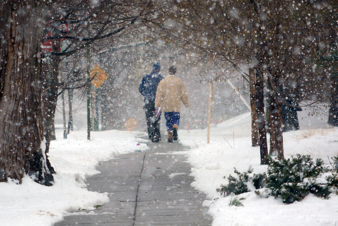 Two people walk along a snow-lined sidewalk in Tenleytown on Tuesday, March 14, 2017. As much as 3 inches of snow fell on the District from a late-winter storm. The decision to open D.C. Public Schools two hours late on Tuesday surprised some partents, but drew a frosty response from some on Twitter. Most schools in the region closed. (WTOP/Dave Dildine)
