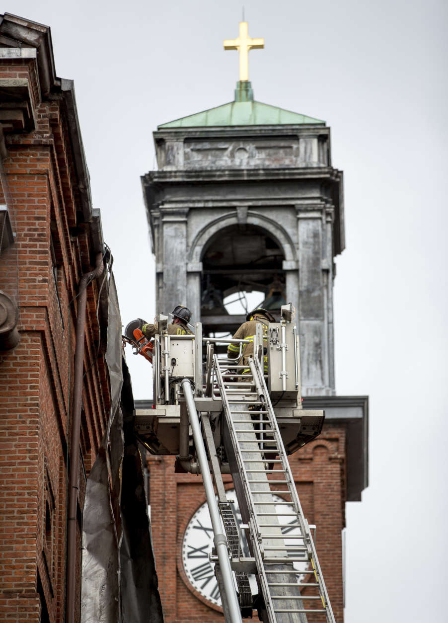 Firefighters work to cut pieces of damaged tin roof down after high winds damaged the roof of St. Aloysius Catholic Church at Gonzaga High School in Washington, Thursday, April 6, 2017. (AP Photo/Andrew Harnik)