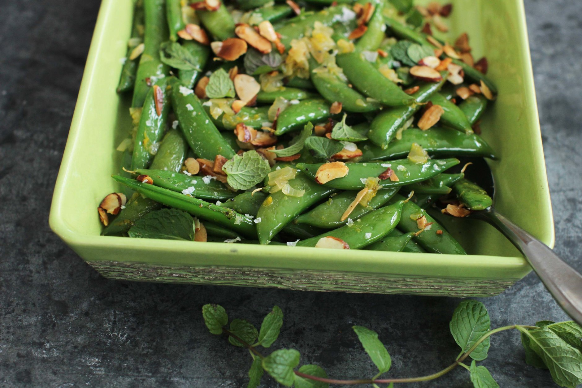This Feb. 8, 2016 photo shows minty sugar snap peas with tangerine and toasted almonds in Concord, N.H. After a long winter of heavy foods, this simple, but delicious dish adds bright flavors and colors to springtime meals. (AP Photo/Matthew Mead)