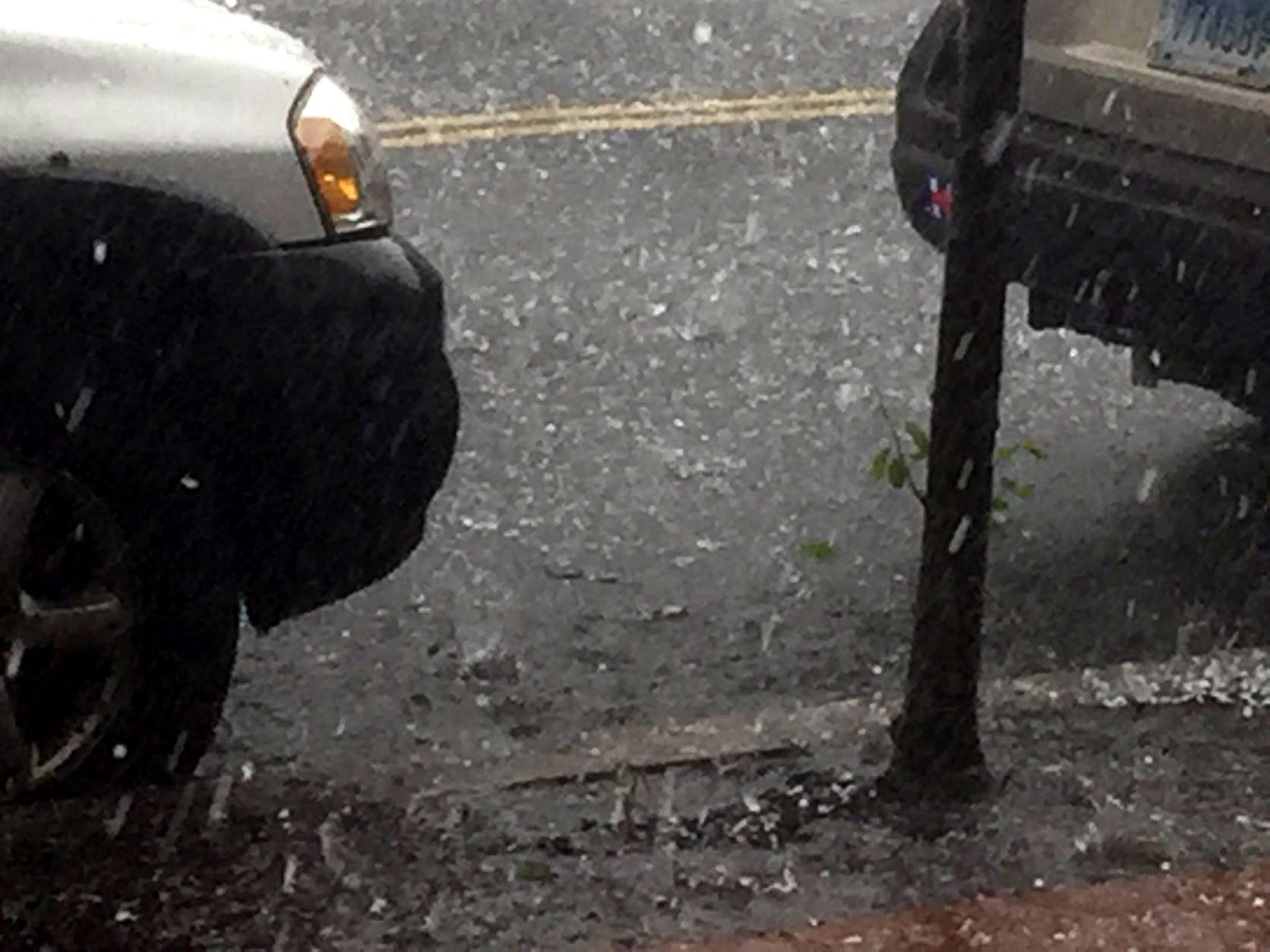Photos of hail falling onto a parked car