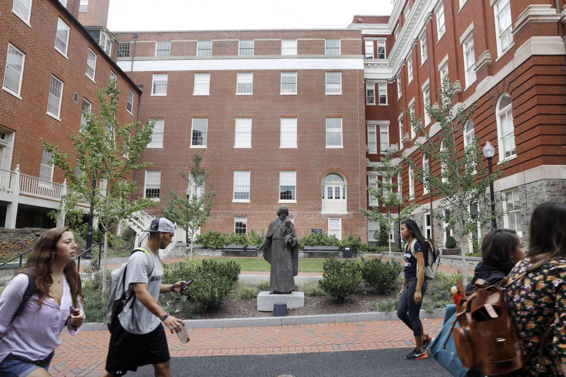 In this Sept. 1, 2016, file photo, students walk past a Jesuit statue in front of Freedom Hall, center, formerly named Mulledy Hall, on the Georgetown University campus, Thursday, Sept. 1, 2016, in Washington. (AP Photo/Jacquelyn Martin, File)