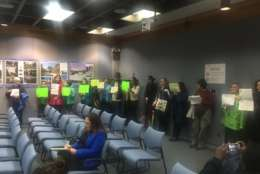 About 20 protesters stood in the back and held signs during the Montgomery County Planning Board's meeting in Silver Spring. (WTOP/John Aaron)