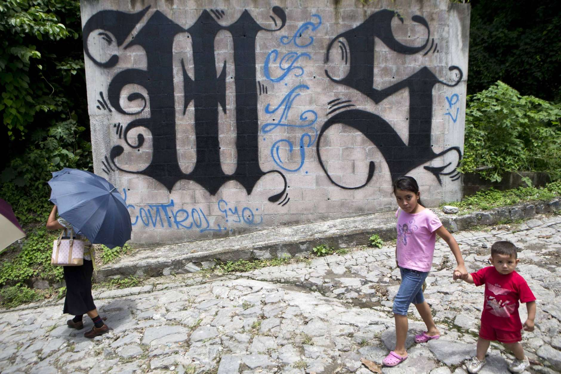 In this Aug. 21, 2014 file photo, a family walks by a wall covered by a symbol from the Mara Salvatrucha, of MS-13 gang in Ilopango, El Salvador. The gang has gained power and prominence in the D.C. area in recent years, and while it's thought of as a Salvadoran and Central American gang, it started in the U.S. (AP Photo/Esteban Felix, File)