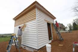 In this Wednesday, April 12, 2017 photo, painters works on the side of a newly constructed slave cabin in the South yard Slave Community at James Madison's Montpelier, in Montpelier, Va. The slave quarters were cleared away more than 150 years ago and planted over with grass. The reconstruction began in 2015 after a gift from David Rubenstein, a Washington philanthropist and history buff. (AP Photo/Steve Helber)'
