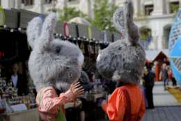 In this Thursday, April 13, 2017, picture entertainers wearing rabbit costumes speak at a fair in Bucharest, Romania. Ahead of Easter, celebrated by both Orthodox and Catholic believers on April 16 processions of priests clad in golden robes carrying foliage on Palm Sunday in a recreation of Jesus' ride into Jerusalem, mixed with more commercial flavored celebrations like an Easter fair outside the giant palace built by late Communist leader Nicolae Ceausescu where entertainers strutted around wearing giant rabbit heads.(AP Photo/Vadim Ghirda)