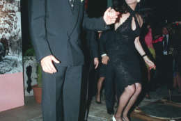 "Actor Don Johnson, left, and Saundra Santiago, co-stars of the TV show ""Miami Vice,"" jump up and down in order to immortalize their footprints in cement to commemorate the show's 100th episode at a party in Miami, Fl., Tuesday night, Feb. 15, 1989.  (AP Photo/Beth Keiser)"