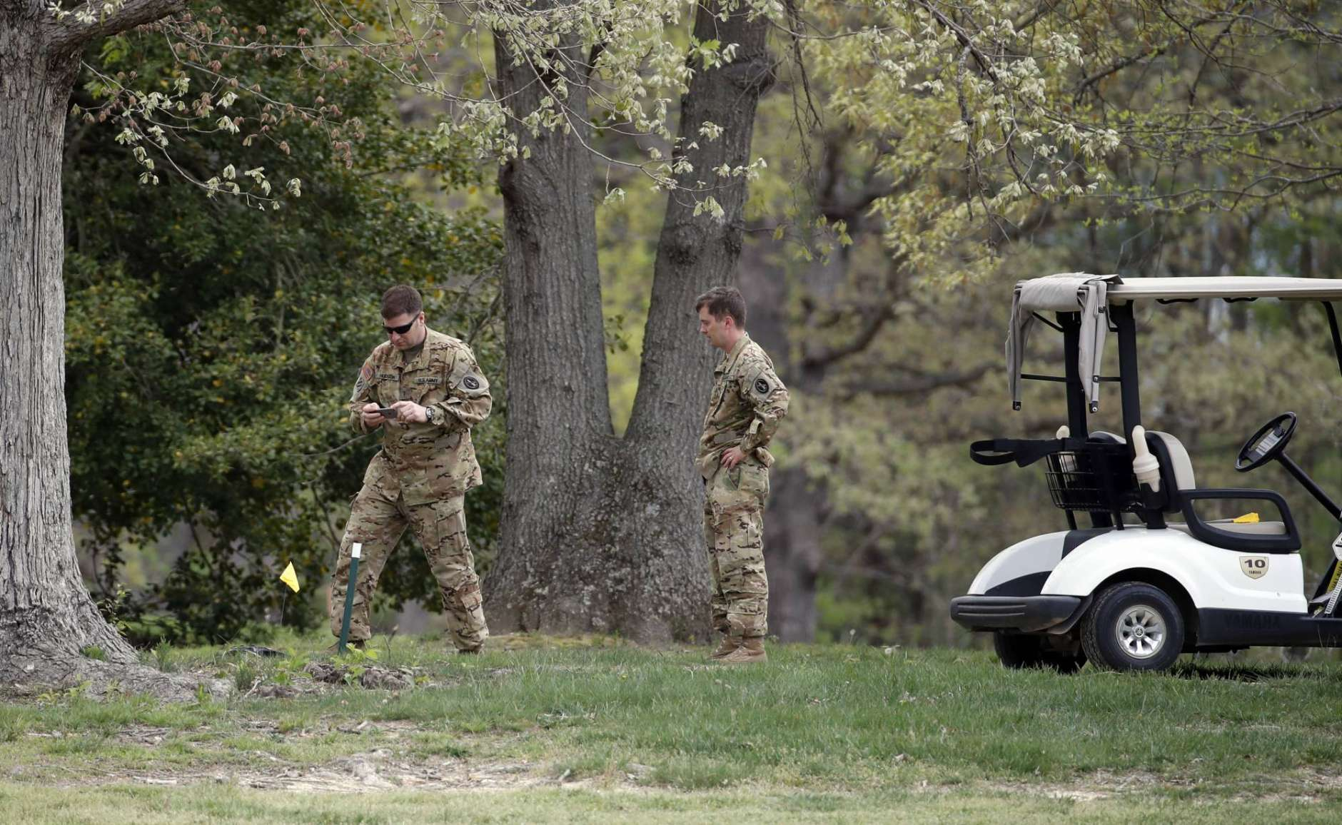 Investigators examine debris that fell on the Breton Bay Golf and Country Club golf course after an Army UH-60 helicopter from Fort Belvoir, Va., crashed, Monday, April 17, 2017, in Leonardtown, Md. (AP Photo/Alex Brandon)
