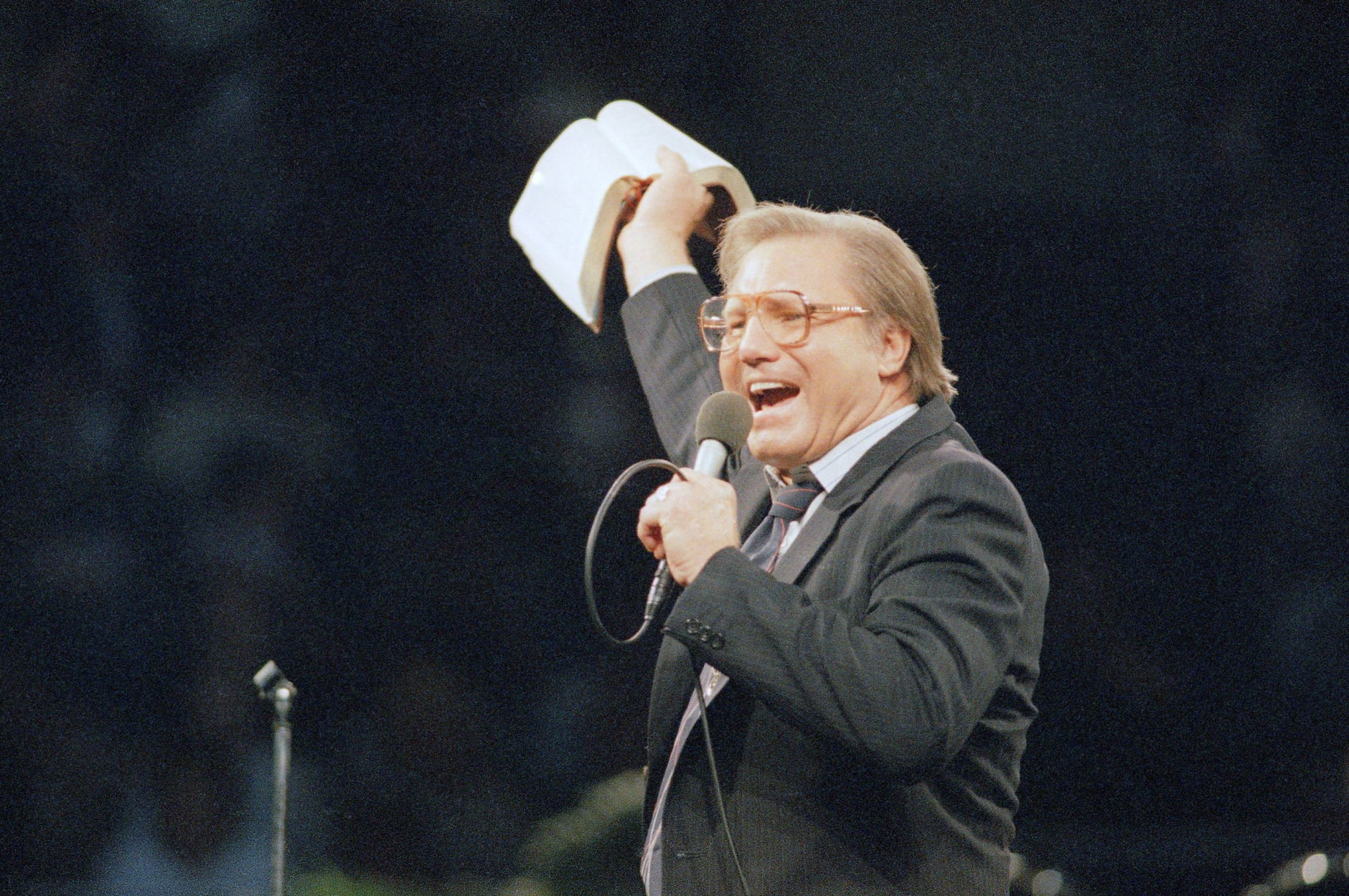The Rev. Jimmy Swaggart gestures with the bible as spread the word of the Lord to the 14,000 faithful that packed the Los Angeles Sports Arena during his Los Angeles Crusade, Sunday, March 30, 1987. (AP Photo/Mark Avery)