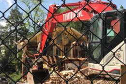Construction crews tear down a posh D.C. house that was the scene of a 2015 quadruple homicide on Friday, April 21, 2017. The house sold for $3 million months after Savvas and Amy Savopoulos, their son Philip and housekeeper Vera Figueroa were killed. (WTOP/Megan Cloherty)