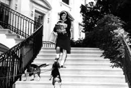 Luci, daughter of president and Mrs. Lyndon Johnson, stops on the White House steps to pet the family's beagles, Him and Her, as she leaves for school on Sept. 17, 1964. It is the first day of classes for Luci, who is in her senior year at National Cathedral School of Girls.(AP Photo)