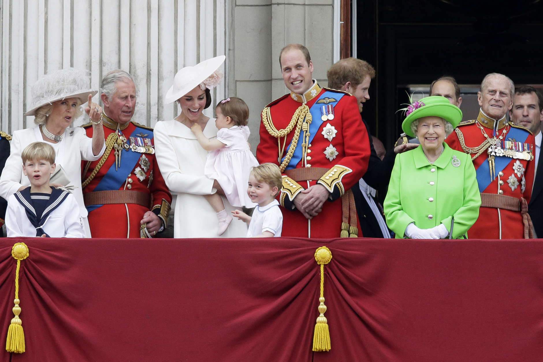 """Britain's Queen Elizabeth II smiles with Prince Philip, right, Prince William, centre, his son Prince George, front, Kate, Duchess of Cambridge holding Princess Charlotte, centre left, The Prince of Wales and The Duchess of Cambridge, left, on the balcony during the Trooping The Colour parade at Buckingham Palace, in London, Saturday, June 11, 2016. Hundreds of soldiers in ceremonial dress have marched in London in the annual Trooping the Colour parade to mark the official birthday of Queen Elizabeth II. The Trooping the Colour tradition originates from preparations for battle, when flags were carried or """"trooped"""" down the rank for soldiers to see. (AP Photo/Tim Ireland)"""