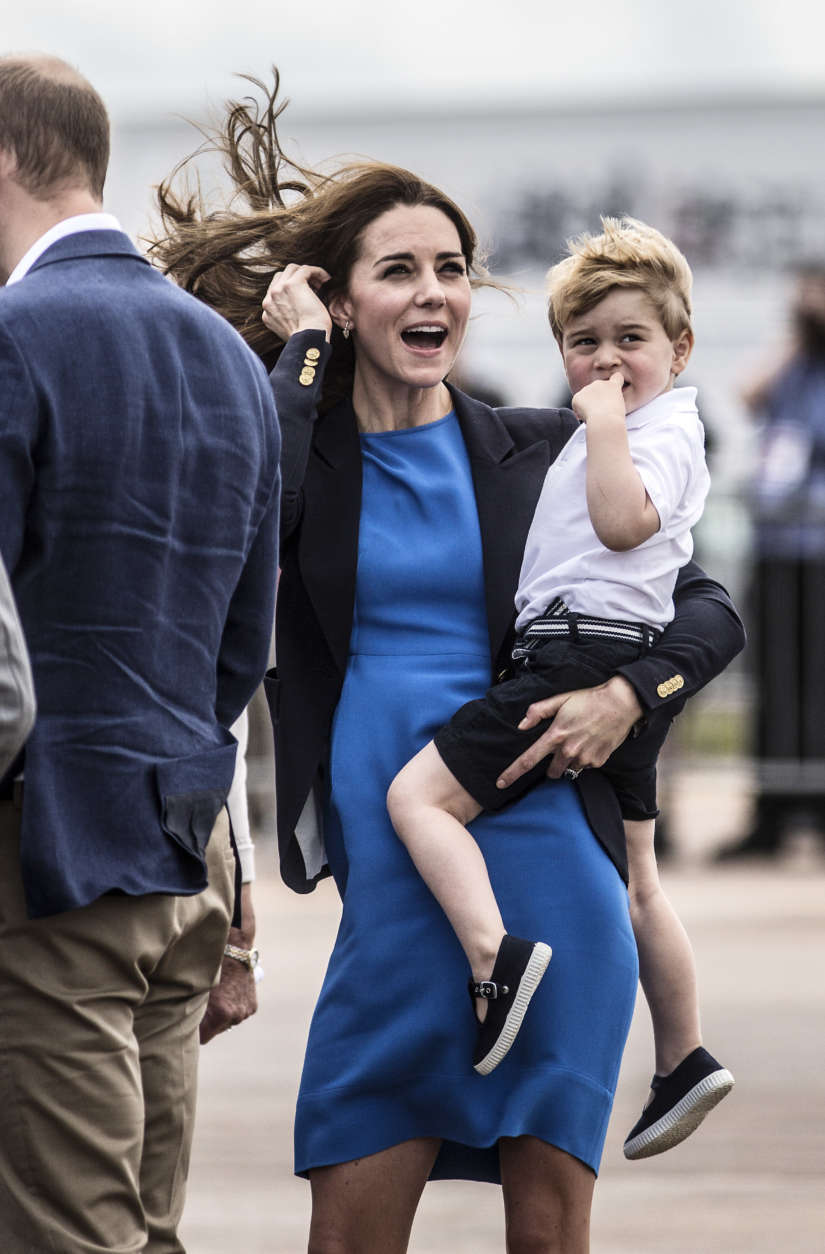 Kate, the Duchess of Cambridge, reacts to a low flying air display as she carries Prince George during a visit to the Royal International Air Tattoo at RAF Fairford in Gloucestershire, England, Friday July 8, 2016. (Richard Pohle/ Pool photo via AP)