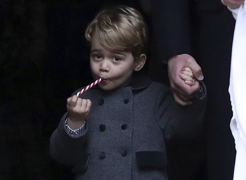 In this Sunday, Dec. 25, 2016 file photo, Prince George eats a sweet as he leaves following the morning Christmas Day service at St Mark's Church in Englefield, England. (Andrew Matthews/Pool via AP, File)