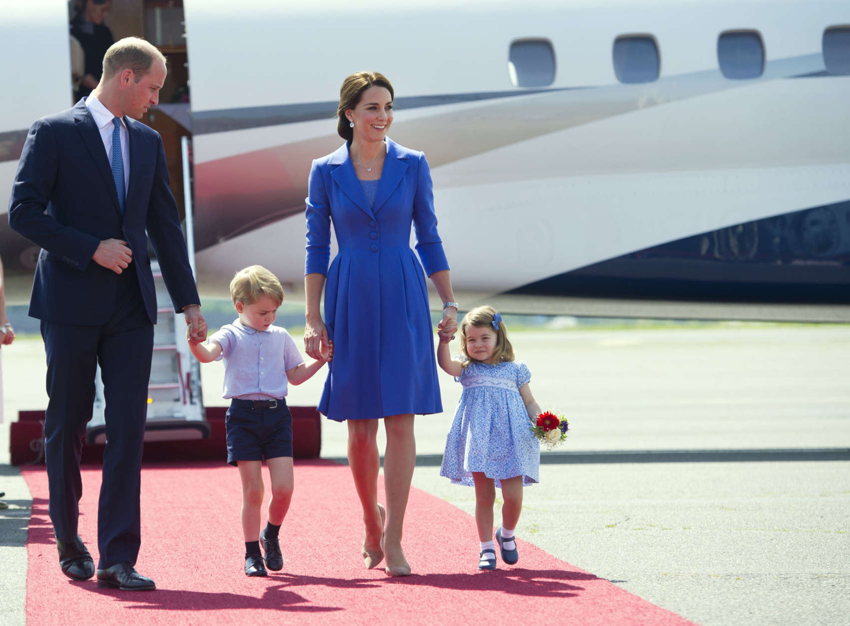 Britain's Prince William, left, Kate, the Duchess of Cambridge and their children Prince George and Princess Charlotte arrive at the airport in Berlin, Wednesday, July 19, 2017. The British royal couple is on a three-day-visit in Germany. (Steffi Loos/Pool Photo via AP)