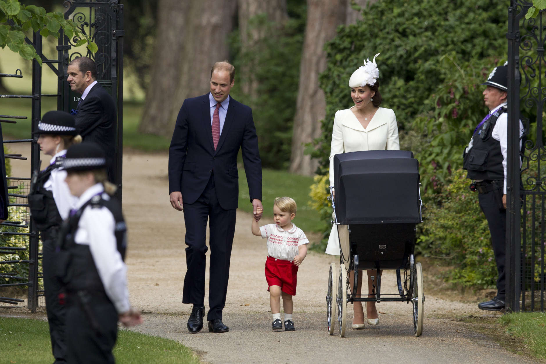 """FILE- In this file photo dated Sunday, July 5, 2015, Britain's Prince William, Kate the Duchess of Cambridge, their son Prince George walk with their daughter Princess Charlotte in a pram, during an official media event as they arrive for Charlotte's Christening at St. Mary Magdalene Church in Sandringham, England.  Royal officials at Kensington Palace are urging all media organizations not to publish images of Prince George and Princess Charlotte, by some paparazzi photographers who are using increasingly dangerous tactics to snap images of the royals, which presents a risk """"in a heightened security environment.'' (AP Photo/Matt Dunham, FILE)"""