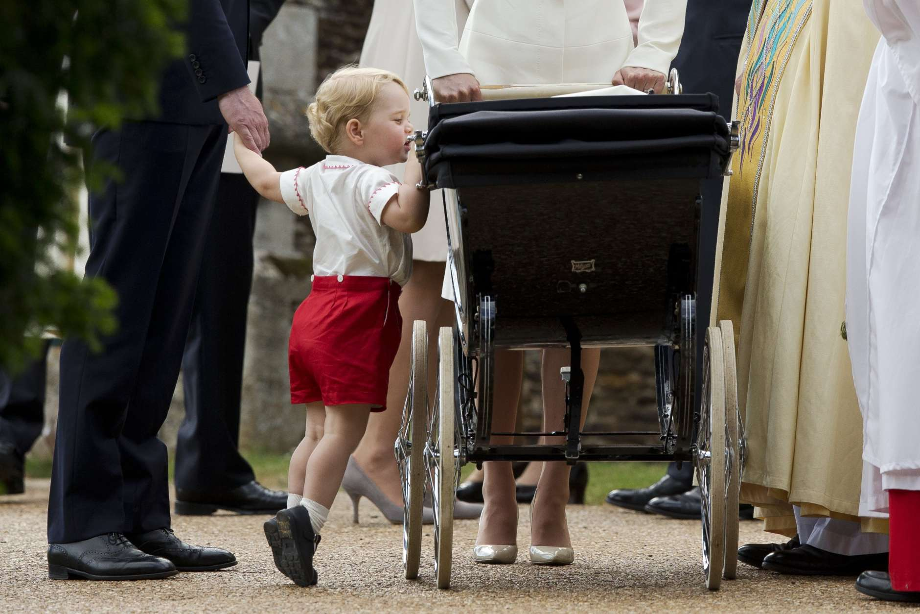 Britain's Prince George gets up on tip-toes to peek into the pram of his sister Princess Charlotte flanked by his parents Prince William and Kate the Duchess of Cambridge as they leave after Charlotte's Christening at St. Mary Magdalene Church in Sandringham, England, Sunday, July 5, 2015.  (AP Photo/Matt Dunham, Pool, File)