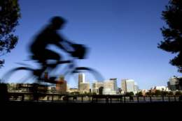 FILE - In this July 10, 2008, file photo, a bicyclist travels along the east bank of the Willamette River in Portland, Ore. As Oregon endures an acute housing shortage, the Legislature is considering making landlords pay tenants for no-cause evictions. The bill would also reverse a law that bans most rent controls, allowing cities and counties to adopt their own rent-controls. (AP Photo/Don Ryan, File)
