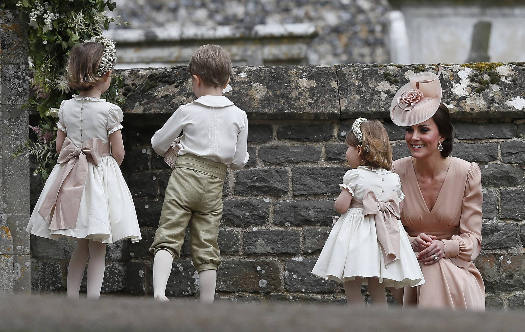 Kate, Duchess of Cambridge, right, smiles as she kneels next to her children Princess Charlotte, second right, and Prince George, who were flower boys and girls at the wedding of Pippa Middleton and James Matthews at St Mark's Church in Englefield, England Saturday, May 20, 2017. Middleton, the sister of Kate, Duchess of Cambridge married hedge fund manager James Matthews in a ceremony Saturday where her niece and nephew Prince George and Princess Charlotte was in the wedding party, along with sister Kate and princes Harry and William. (AP Photo/Kirsty Wigglesworth, Pool)