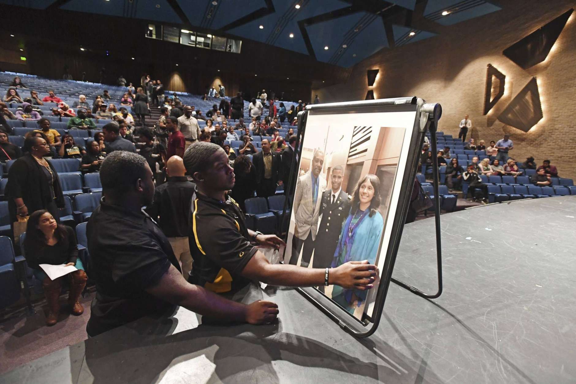 Marquise Wade, from left, sophomore class president, and Darrin Branch, coordinator of Greek Life on campus, set up a picture of Richard Collins III for a memorial vigil for Collins, who was killed Saturday at the University of Maryland in College Park, as they gather at Bowie State's auditorium in Bowie, Md., Monday, May 22, 2017. Authorities appealed for patience Monday from two college communities reacting in shock, fear and anger after a white University of Maryland student was arrested in what police called the unprovoked stabbing of a black Bowie State University student. (Kenneth K. Lam/The Baltimore Sun via AP)