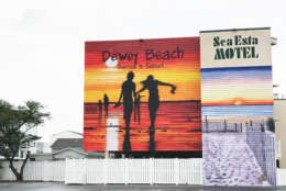 Even on a gray day, the bright orange and yellow mural on one of the many Sea Esta Motel buildings welcomes visitors to Dewey Beach. (WTOP/Megan Cloherty)