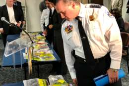 D.C. Police Chief Peter Newsham surveys the illegal firearms pulled off the streets and packaged in evidence bags after a press conference May 10, 2017. (WTOP/Megan Cloherty)