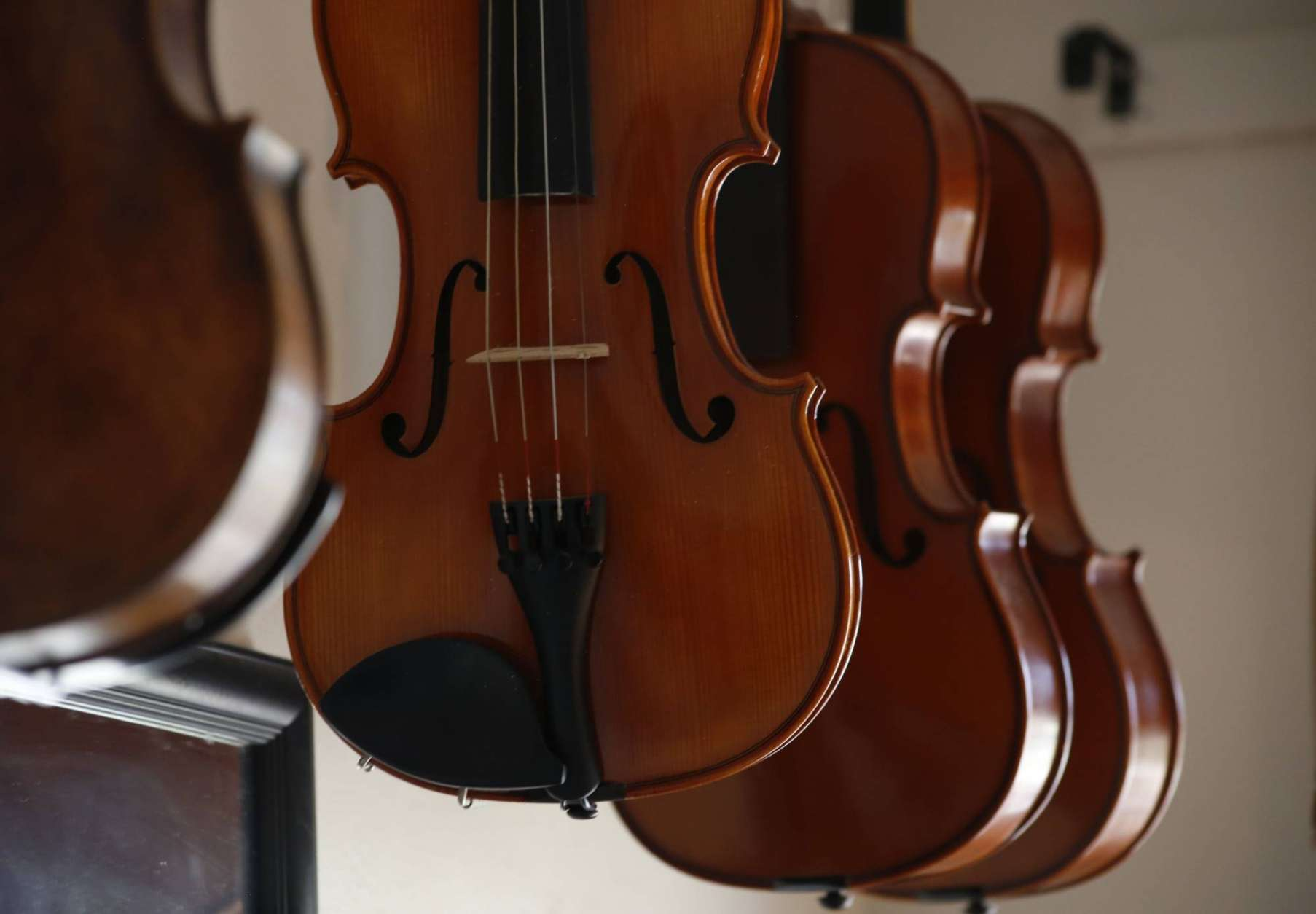 Violins hang in the workshop in Sonja St. John's Neenah, Wis., home on Monday, May 8, 2017. Her brother, Jon St. John died in 2007 in the Iraq war. Among other things, Sonja has found solace in her career, making and restoring violins. (AP Photo/Martha Irvine)