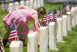 Angelina Cruz, 8, lays flags in remembrance for military members lost in war at various gravestones during Memorial Day at the Evergreen Cemetery on Monday, May 29, 2017, in Colorado Springs, Colo.  (Dougal Brownlie/The Gazette via AP)